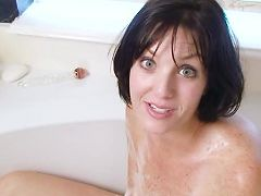 Dark haired milf with tan lines fucks a dildo in the bath tub